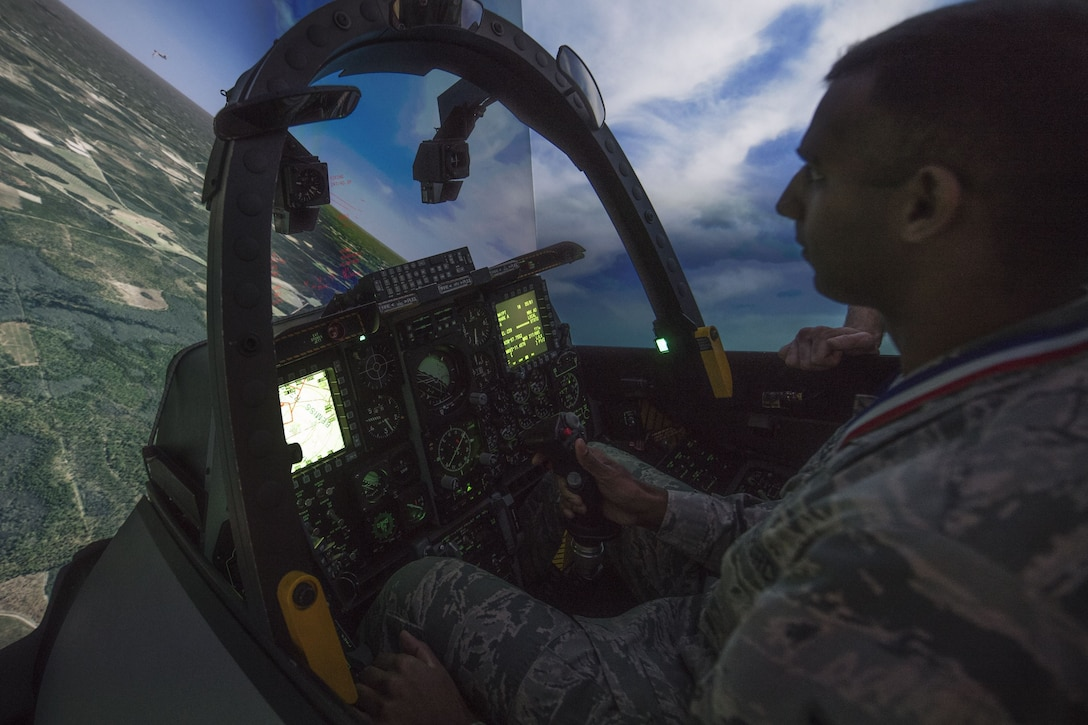 Senior Airman Andrew Soarez, 23d Medical Support Squadron medical laboratory technician, flies in an A-10C Thunderbolt II simulator during a Tour of Champions, Feb. 2, 2018, at Moody Air Force Base, Ga. The Tour of Champions recognizes 23d Wing annual award nominees and an opportunity to gain a better perspective of the 23d Wing's mission. (U.S. Air Force photo by Senior Airman Daniel Snider)