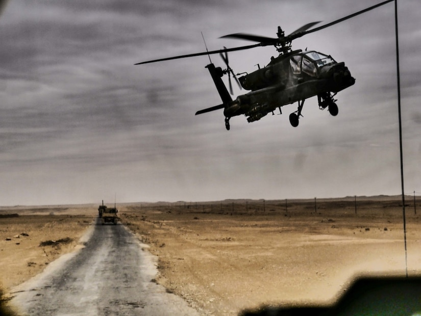 An AH-64 Apache helicopter flies over a convoy in Iraq.