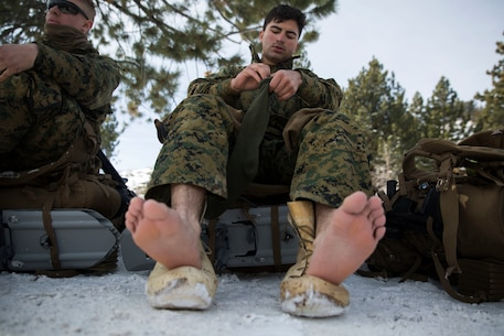 Cpl. Daniel Aldana, a distribution specialist with Combat Logistics Regiment 25, 2nd Marine Logistics Group changes his socks during a tactical pause on a hike during cold weather training at Marine Corps Mountain Warfare Training Center in Bridgeport, Calif., Jan. 26, 2018. Approximately 90 Marines participated in the week-long event where they learned survival skills, how to traverse mountainous terrain and cold weather weapons maintenance. The training will prepare the Marines for joint-force training exercise Artic Edge in northern Alaska, which will expose Marines to the peninsula's weather extremes. (U.S. Marine Corps photo by Sgt. Brianna Gaudi)
