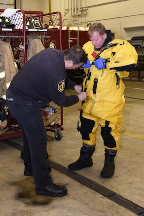 Gary Stringer helps Ed Hirth, both firefighters with the 127th Civil Engineer Squadron, assigned to the Selfridge Air National Guard Base fire department, don a cold-water emergent suit to prepare for an ice rescue training exercise on Lake St. Clair, Harrison Township, Mich. on Jan. 31, 2017.