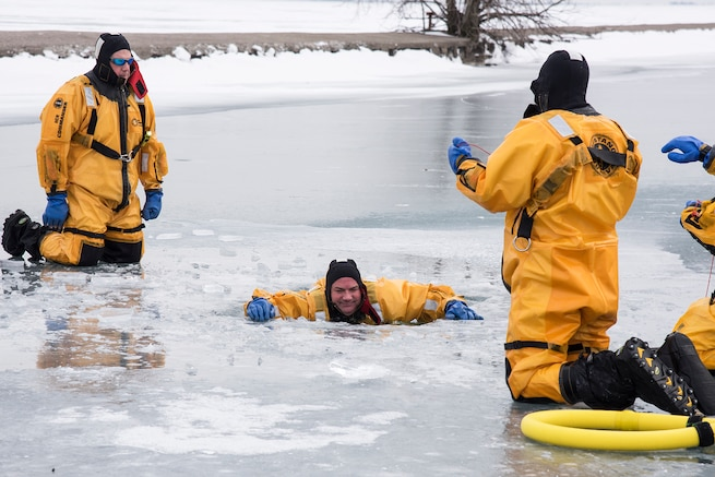 Dave Long and Joe Zydel, firefighters with the 127th Civil Engineer Squadron, assigned to the Selfridge Air National Guard Base fire department, practice self-rescue techniques during an ice rescue training exercise on Lake St. Clair, Harrison Township, Mich. on Jan. 31, 2017.