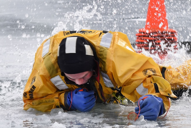 A firefighter with the 127th Civil Engineering Squadron, assigned to the Selfridge Air National Guard Base Fire Department practices using ice awls to extricate himself from hole during an ice rescue training exercise on Lake St. Clair, Harrison Township, Mich. on Jan. 31, 2017.