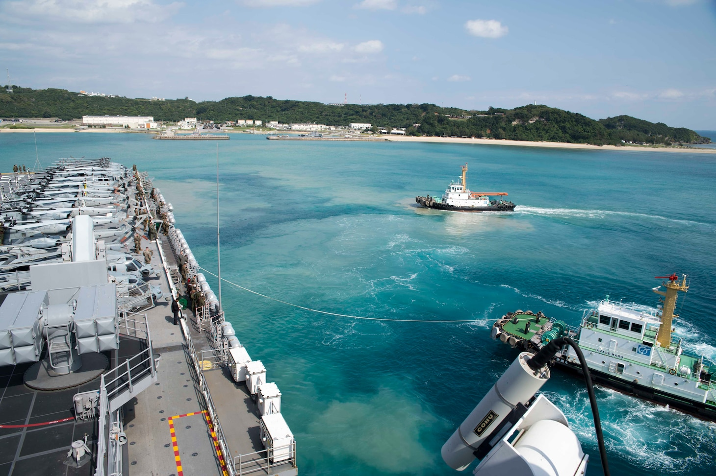 180202-N-XK809-013 WHITE BEACH, Okinawa (Feb. 2, 2018) A tug boat guides the amphibious assault ship USS Bonhomme Richard (LHD 6) away from the pier during the ship's departure from White Beach Naval Facility, Okinawa. Bonhomme Richard is operating in the Indo-Asia-Pacific region as part of a regularly scheduled patrol and provides a rapid-response capability in the event of a regional contingency or natural disaster. (U.S. Navy photo by Mass Communication Specialist 2nd Class William Sykes/Released)