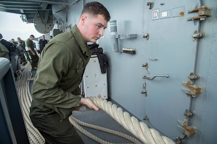 HITE BEACH, Okinawa (Feb. 2, 2018) Lance Cpl. Brandon Rudde, from Independence, Ky., heaves a line during sea and anchor detail aboard the amphibious assault ship USS Bonhomme Richard (LHD 6) as the ship departs White Beach Naval Facility, Okinawa.