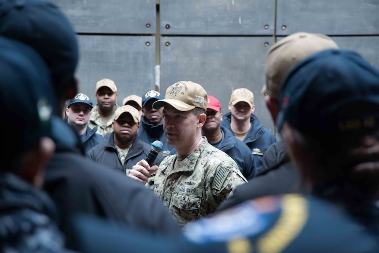 Rear Adm. Brad Cooper, commander of Amphibious Force 7th Fleet, speaks to Sailors aboard the amphibious dock landing ship USS Germantown (LSD 42) during an all hands call.