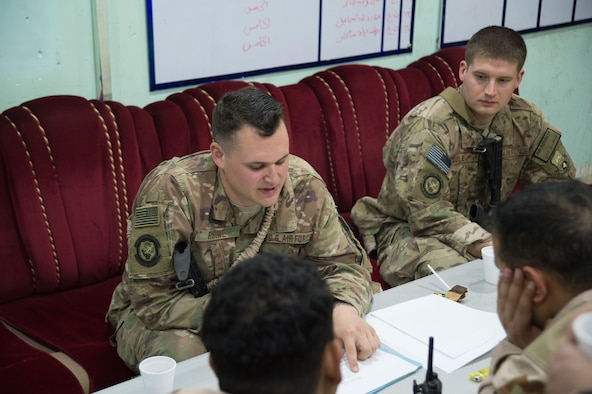 Staff Sgt. Dakota Rhine, 442nd Air Expeditionary Squadron noncommissioned officer in charge of the Baghdad aerial port (left) and Staff Sgt. Timothy Riddle, 370th Air Expeditionary Advisory Squadron air advisor, review revised technical and training manuals with Iraqi Air Force Airmen in Baghdad Jan. 16, 2018. Air advisors support the Combined Joint Task Force - Operation Inherent Resolve through an advise and assist mission, which consists of a small team working alongside Iraqi Airmen in day-to-day airfield operations. (U.S. Air Force photo by Staff Sgt. William Banton)