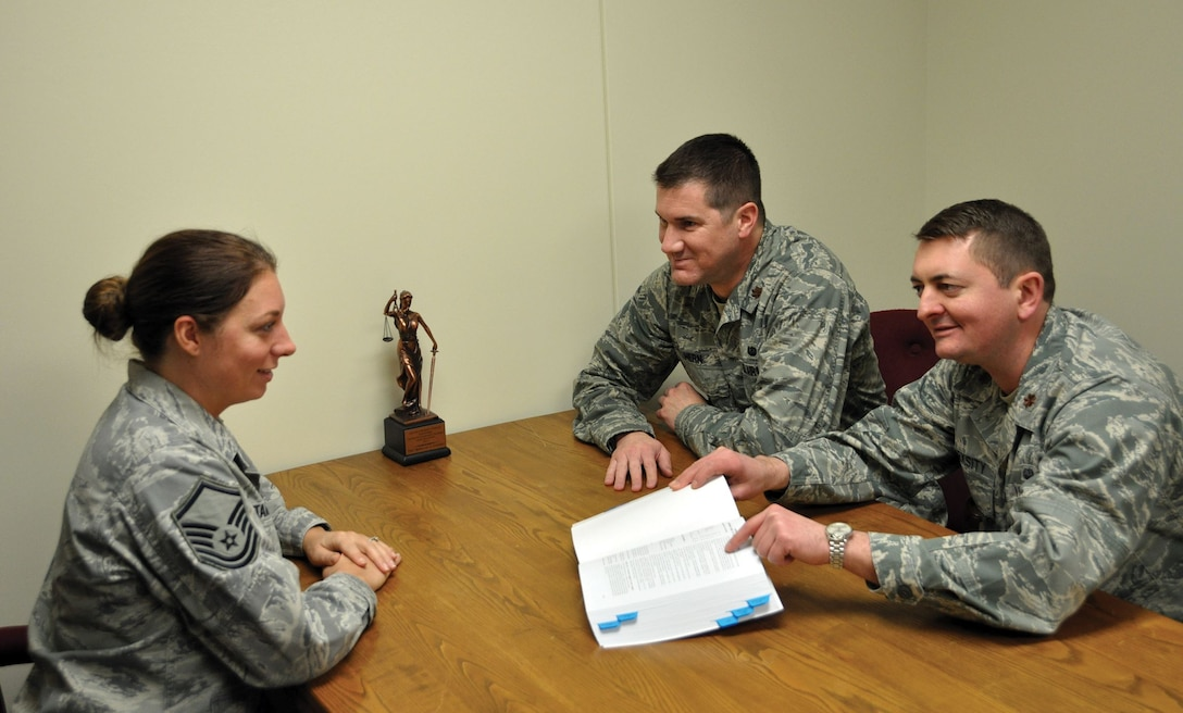 Master Sgt. Rebeccah Stammen, law office superintendent, reviews military legal guidance with Majs. (right) Drew Marksity, adverse actions chief, and Kyle Hern, deputy staff judge advocate, Jan. 7, 2018