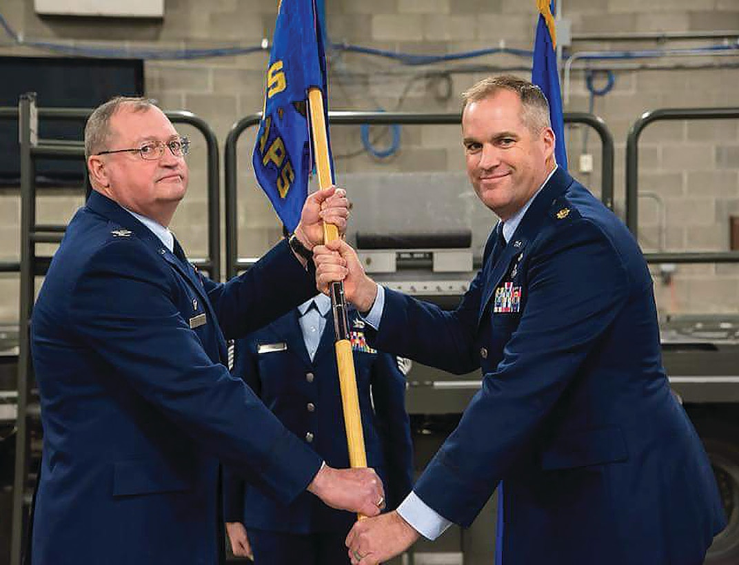 Col. Bryan Runion, 445th Mission Support Group commander, passes the guidon to Maj. David Borden, incoming 87th Aerial Port Squadron commander, during the January 6, 2018 change-of command ceremony