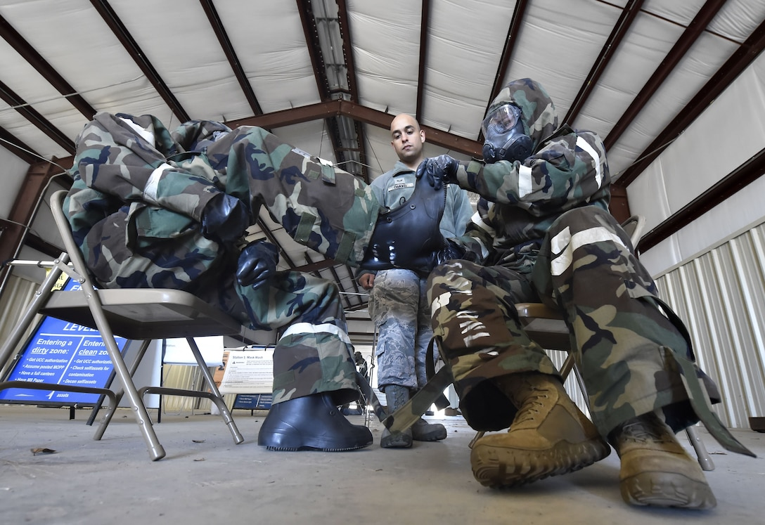 Senior Airman Paul Chavis III, center, 628th Civil Engineer Squadron, familiarizes Airmen of the 621st Contingency Response Wing, Joint Base McGuire-Dix-Lakehurst, New Jersey, with chemical, biological, radiological and nuclear defense techniques during Exercise Crescent Moon Jan. 30, at Joint Base Charleston's North Auxiliary Airfield near Orangeburg, South Carolina.