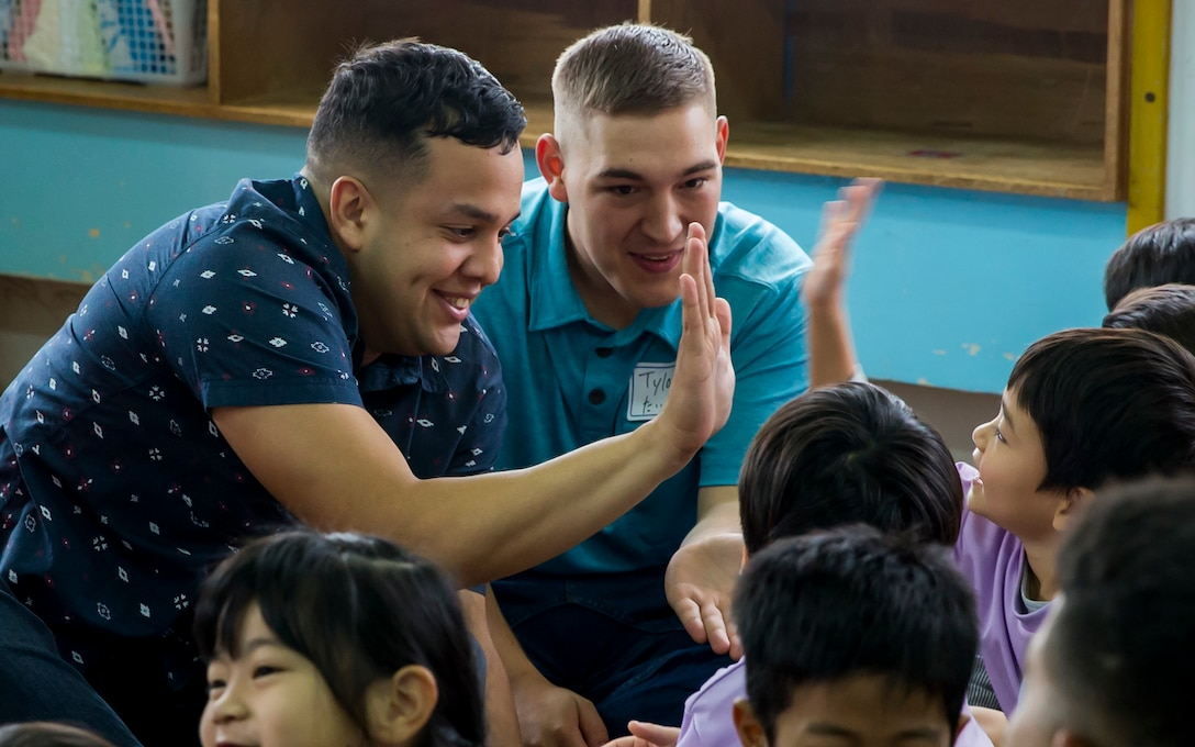 U.S. Marine Corps Lance Cpl. Headley Hall (left) and Petty Officer 3rd Class Tylor Tharp (right) high five children during a visit to Namisato Preschool in Okinawa, Japan, Jan. 30, 2018. Marines visited the school for a community relations event that helps the children learn basic English. Hall, a Chicago native, is an administrative clerk and Tharp, a St. Augustine, Florida native, is a religious program specialist. Both Marines are with Headquarters and Service Company, 3rd Battalion, 3rd Marine Regiment, 3rd Marine Division. The Marines continue fostering relations with the local population and building bonds with allies.