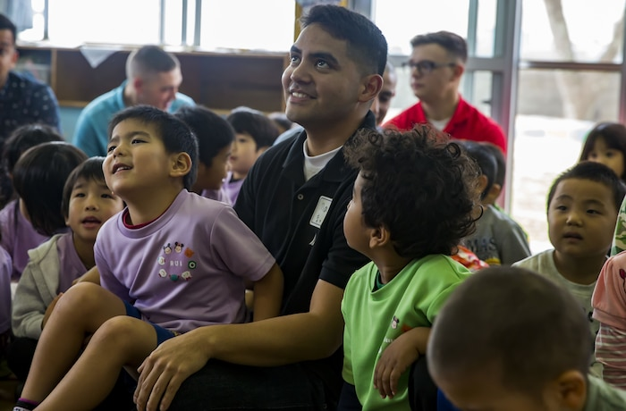 U.S. Marine Corps Cpl. Mac Sautia sits with children during a visit to Namisato Preschool in Okinawa, Japan, Jan. 30, 2018. Marines visited the school during a community relations event to help children learn basic English. Sautia, an Oceanside, California native, is a radio technician with Headquarters and Service Company, 3rd Battalion, 3rd Marine Regiment, 3rd Marine Division. Marines continue fostering relations with the local population and building bonds with allies.