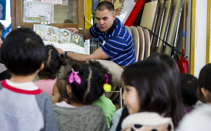 U.S. Marine Corps Cpl. Darren Broughton reads Where the Wild Things Are to children during a visit to Namisato Preschool in Okinawa, Japan, Jan. 30, 2018. Marines visited the school as a community relations event that helps the children learn basic English. Broughton, an Odessa, Texas native, is a team leader with Kilo Company, 3rd Battalion, 3rd Marine Regiment, 3rd Marine Division.. Marines continue fostering relations with the local population and building bonds with allies.