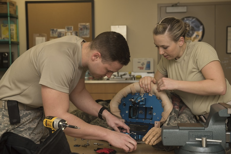 U.S. Air Force Airmen 1st Class Cody Knoll, left, and Jennifer Lesley, 20th Medical Support Squadron biomedical equipment technicians, take apart a trauma dummy prior to accomplishing a repair at Shaw Air Force Base, S.C., Jan. 31, 2018.
