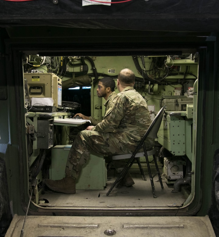 Army Sgt. Darryl Griffith, looking at a computer screen, tracks, manages and relays data to fire support assets from the fire direction center during a live-fire training exercise at Grafenwoehr Training Area, Germany, Feb. 2, 2018. Griffith is a fire support specialist assigned to 1st Battalion, 7th Field Artillery Regiment. Army photo by Staff Sgt. Sharon Matthias