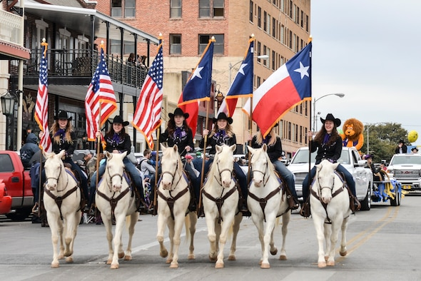 Six white horses and their riders carry American and Texas flags during the rodeo parade in San Angelo, Feb. 3. 2018. The rodeo parade featured 100 entries and included members of the Sante Fe Trail Ride, various floats from clubs and community organizations, antique tractors and local horse clubs. (U.S. Air Force photo by Aryn Lockhart/Released)