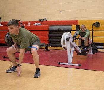 Master Sgt. Jeremy Owens, battalion logistics chief, Headquarters and Service Battalion, U.S. Marine Corps Forces Command, squats with a resistance band while Sgt. James Toney, security specialist, MARFORCOM, uses the rowing machine during a High Intensity Tactical Training session at Hopkins Hall Gym aboard Camp Allen, Va., Feb. 1. Marines worked with a partner, switching between exercises at each station. (Official U.S. Marine Corps photo by Chris Jones/Released)