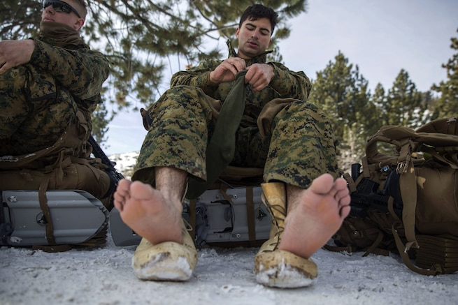 A Marine perches his bare feet on his boots while sitting on gear and changing his socks in the snow.
