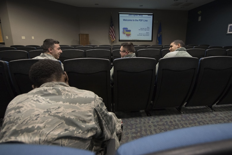 U.S. Airmen interact prior to receiving deployment briefs during a Phase I exercise at Shaw Air Force Base, S.C., Feb. 4, 2018.