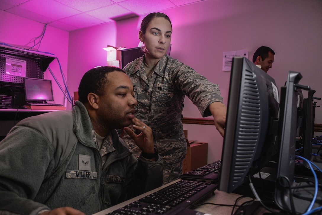 Airman 1st Class Tevin Miller and Airman 1st Class Amanda Button, 707th Communications Squadron client system technicians, update software for computers that will be used on Air Force networks January 9, 2018 at Fort George G. Meade, Maryland. The 707th CS, aligned under the 70th Intelligence, Surveillance and Reconnaissance Wing, supports more than 5,700 global personnel and 57 National Security Agency missions with their 230 'Thunder Warriors.' (U.S. Air Force photo/Staff Sgt. Alexandre Montes)