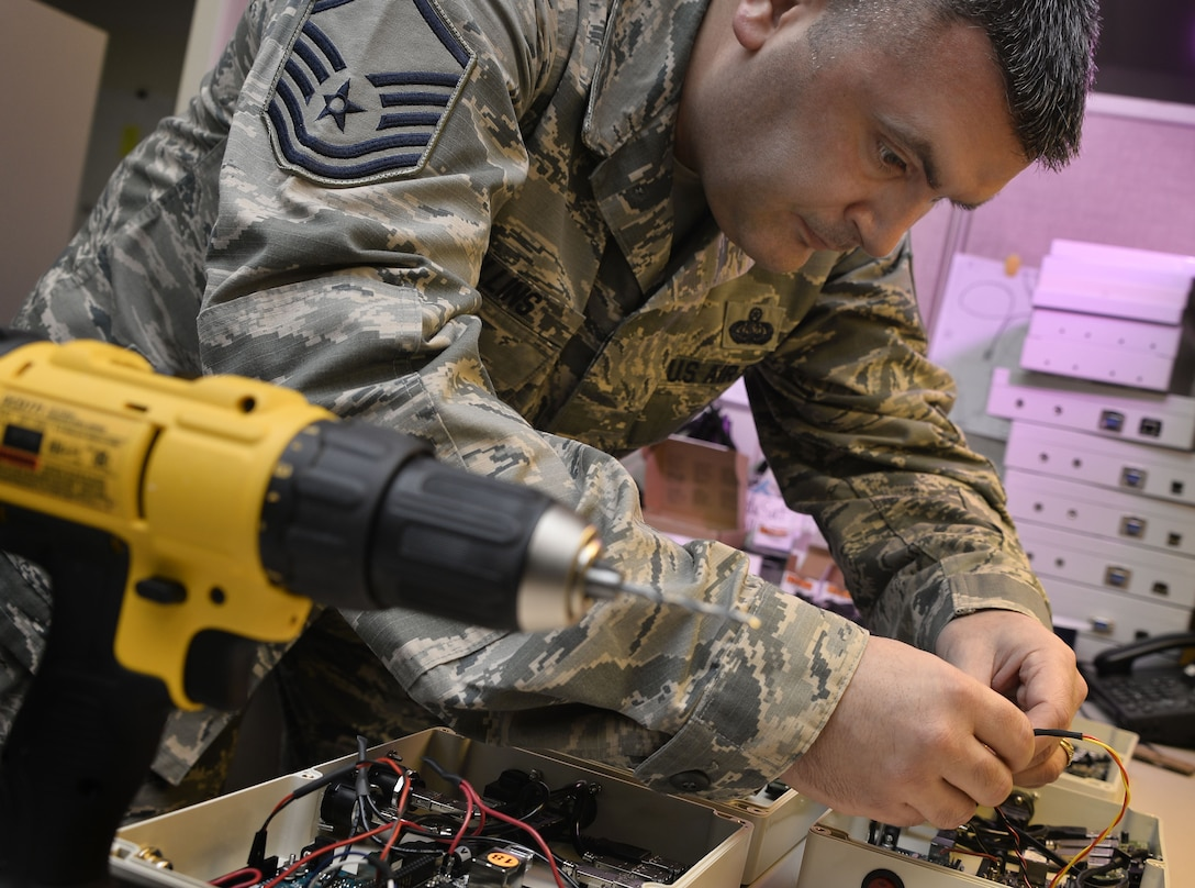 Master Sgt. Jerome Collins, 707th Communications Squadron Special Missions Flight, repairs wiring on a CubeSat control console Jan. 16, 2018, in Laurel, Maryland. The 707th CS, aligned under the 70th Intelligence, Surveillance and Reconnaissance Wing, supports more than 5,700 global personnel and 57 National Security Agency missions with their 230 'Thunder Warriors.' (U.S. Air Force photo/Staff Sgt. Alexandre Montes)