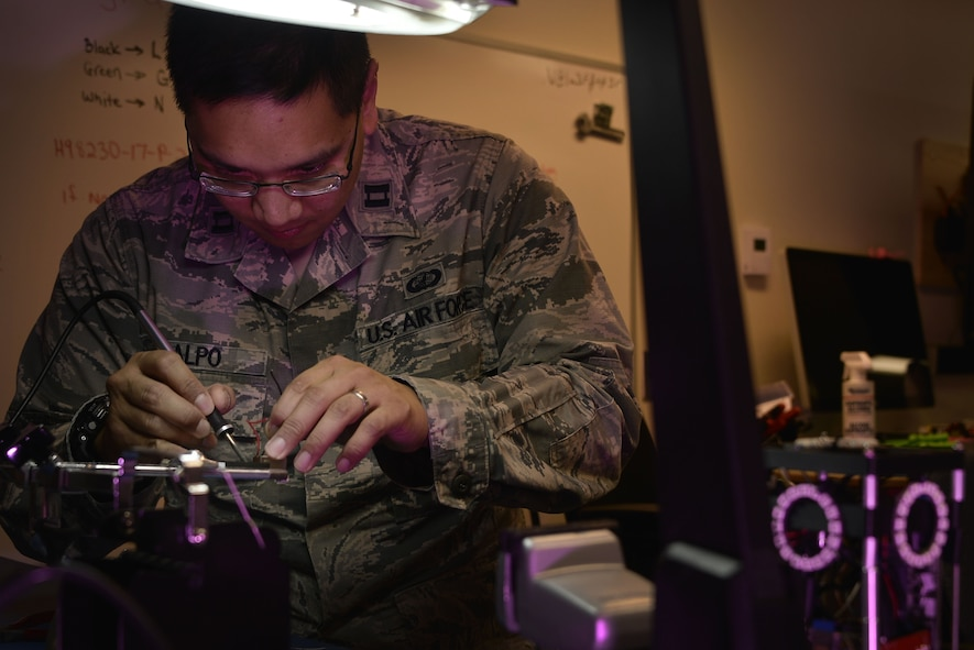 Capt. JBernard Calpo, 707th Communications Squadron Special Missions Flight, repairs a connection on a CubeSat Jan. 16, 2018, in Laurel, Maryland. The 707th CS, aligned under the 70th Intelligence, Surveillance and Reconnaissance Wing, supports more than 5,700 global personnel and 57 National Security Agency missions with their 230 'Thunder Warriors.' (U.S. Air Force photo/Staff Sgt. Alexandre Montes)