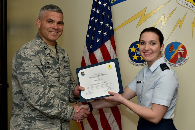 U.S. Air Force Col. Alex Ganster, 17th Training Group commander, presents the 315th Training Squadron Officer Student of the Month award for Jan. 2018 to 2nd Lt. Abigail Paxton, 315th TRS trainee, in the Brandenburg Hall on Goodfellow Air Force Base, Texas, Jan. 2, 2018. The 315th Training Squadron's vision is to develop combat-ready intelligence, surveillance and reconnaissance professionals and promote an innovative squadron culture and identity unmatched across the United States Air Force.
