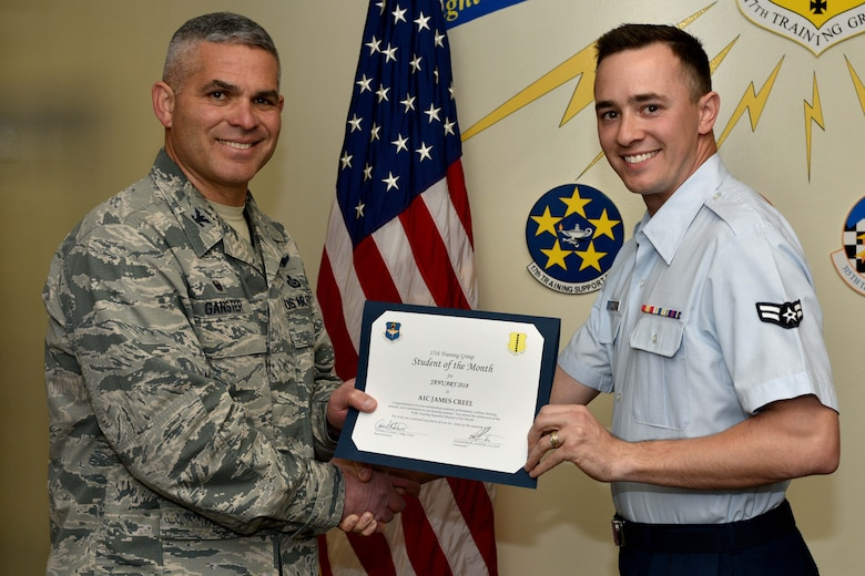U.S. Air Force Col. Alex Ganster, 17th Training Group commander, presents the 312th Training Squadron Student of the Month award for Jan. 2018 to Airman 1st Class James Creel, 312th TRS trainee, in the Brandenburg Hall on Goodfellow Air Force Base, Texas, Jan. 2, 2018. The 312th TRS's mission is to provide Department of Defense and international customers with mission ready fire protection and special instruments graduates and provide mission support for the Air Force Technical Applications Center.
