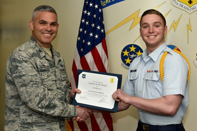 U.S. Air Force Col. Alex Ganster, 17th Training Group commander, presents the 315th Training Squadron Student of the Month award for Jan. 2018 to Airman Calvin Loebrich, 315th TRS trainee, in the Brandenburg Hall on Goodfellow Air Force Base, Texas, Jan. 2, 2018. The mission of the 17th Training Group is to Train, Develop and Inspire Professional Fire Protection and Intelligence, Surveillance and Reconnaissance Warriors.