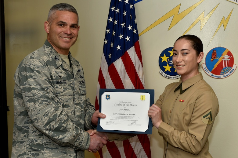 U.S. Air Force Col. Alex Ganster, 17th Training Group commander, presents the 316th Training Squadron Student of the Month award for Jan. 2018 to U.S. Marine Corps Lance Cpl. Stephanie Napier, Marine Corps Detachment at Goodfellow trainee, in the Brandenburg Hall on Goodfellow Air Force Base, Texas, Jan. 2, 2018. The 316th Training Squadron's mission is to conduct U.S. Air Force, U.S. Army, U.S. Marine Corps, U.S. Navy and U.S. Coast Guard cryptologic, human intelligence and military training.