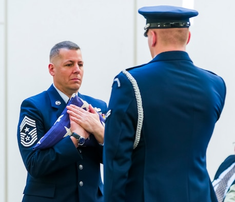 AFOSI Command Chief Master Sgt. #15 Christopher J. VanBurger, accepts the United States Flag from a member of the JBA Honor Guard during Chief VanBurger's retirement ceremony at Quantico, Va., Jan. 26, 2018. (U.S. Air Force photo by Michael Hastings)