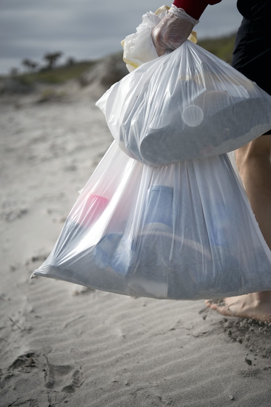A volunteer carries bags of debris to the designated disposal area at Patrick Air Force Base's Beach House on Feb. 3, 2018. Patrick's Airman Leadership School class held a volunteer beach clean-up event in an effort to make Space Coast beaches a more community-friendly environment. (U.S. Air Force photo by Airman Zoe Thacker)