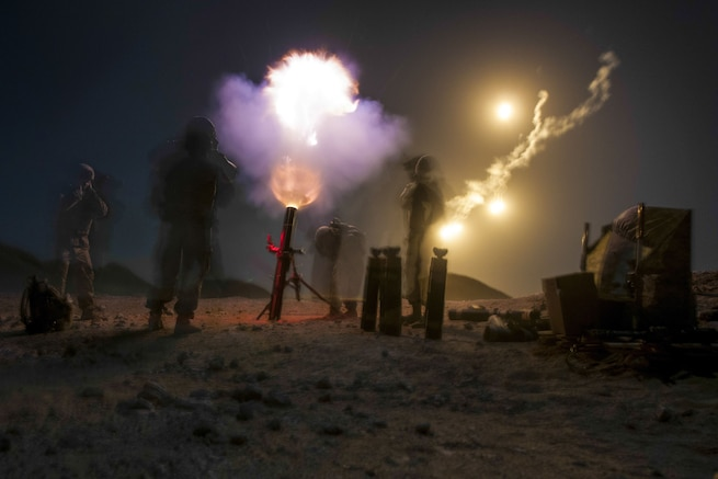 A blast from a mortar lights up the night sky, as soldiers stand by the weapon.