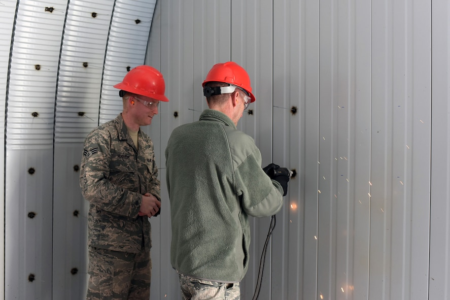 U.S. Air Force Maj. Gen. Scott J. Zobrist, right, 9th Air Force commander, welds a pin to support insulation for a K-Span storage facility at Malmstrom Air Force Base, Mont., while Senior Airman Seth Huguelet discusses welding techniques Jan. 25, 2018. Huguelet is among a team of 819th Rapid Engineer Deployable Heavy Operational Repair Squadron Engineers (RED HORSE) building a K-Space facility which will store RED HORSE equipment. RED HORSE Airmen capitalize on construction opportunities while at home to maintain proficiency for their overseas missions. (U.S. Air Force photo by Kiersten McCutchan)