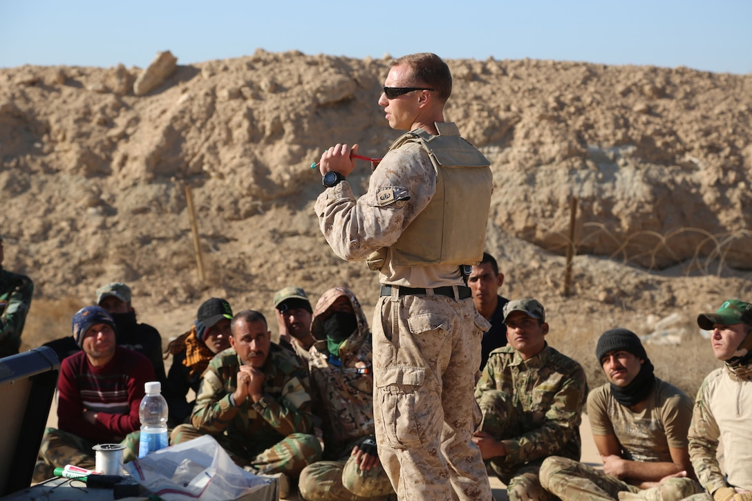 A Marine stands and speaks to foreign troops sitting on ground in front of him.
