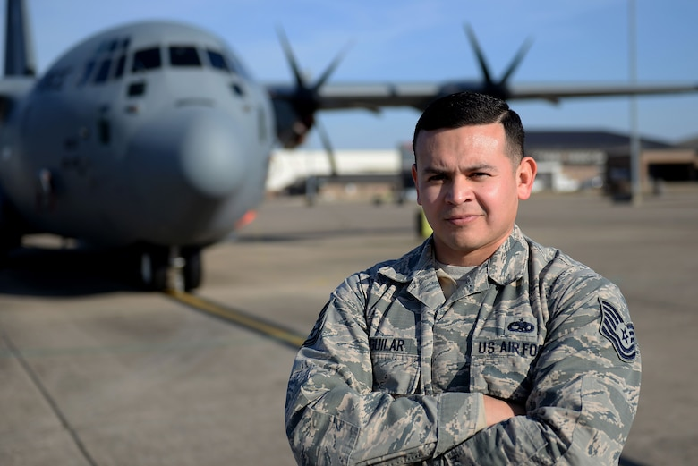 A man in the Air Force Battle Uniform stands with his arms folded in front of a C-130J.