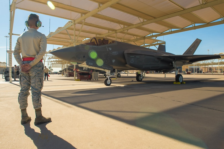 A crew chief assigned to the 63rd Aircraft Maintenance Unit prepares to marshal out an F-35A Lightning II for take-off at Luke Air Force Base, Ariz., Feb. 1, 2018. This year was the first time the F-35 participated in the Haboob Havoc, a fighter pilot competition, hosted by Thunderbolts. (U.S. Air Force photo/Airman 1st Class Caleb Worpel)