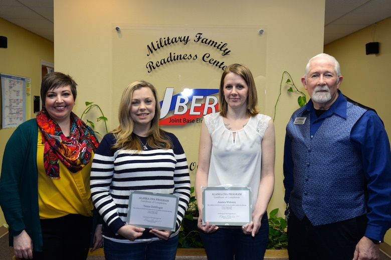Christie Rodriguez, employment readiness program manager and Michael Baty, a community readiness specialist from the Military & Family Readiness Center, stand with Air Force Aid Society Spouse Employment Program scholarship recipients, Tanya Dettlinger and Jessica Walosin, at Joint Base Elmendorf-Richardson, Alaska, Jan. 30, 2018. The MFRC at JBER annually searches and applies for scholarships and grants to provide military spouses with new employment opportunities.