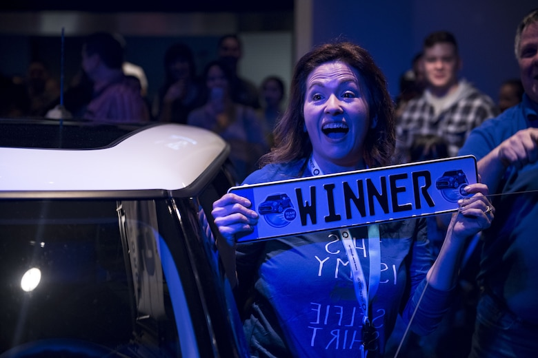 """Yvonne Higby, Vogelweh Elementary School employee, holds a """"winner"""" license plate during the 86th Force Support Squadron's Year of Giving Back Finale at the Enlisted Club on Ramstein Air Base, Germany, Feb. 2, 2018. After winning the 2018 Mini Cooper, Higby described the feeling as overwhelming and thanked the 86th FSS for the gift. (U.S. Air Force photo by Senior Airman Devin Boyer)"""