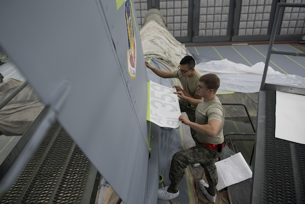 U.S. Air Force Airman 1st Class Roman Estrada, 20th Equipment Maintenance Squadron (EMS) corrosion apprentice, left, and Senior Airman Skylar Braden, 20th EMS corrosion journeyman, use stencils to measure where decals on an F-16CM Fighting Falcon would be placed at Shaw Air Force Base, S.C., Feb. 1, 2018.