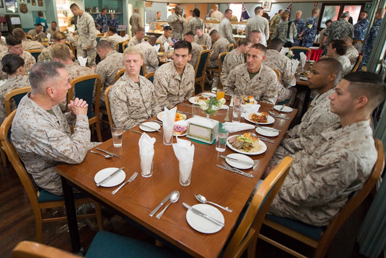 The Chairman of the Joint Chiefs of Staff meets with Marines during a meal in Australia.