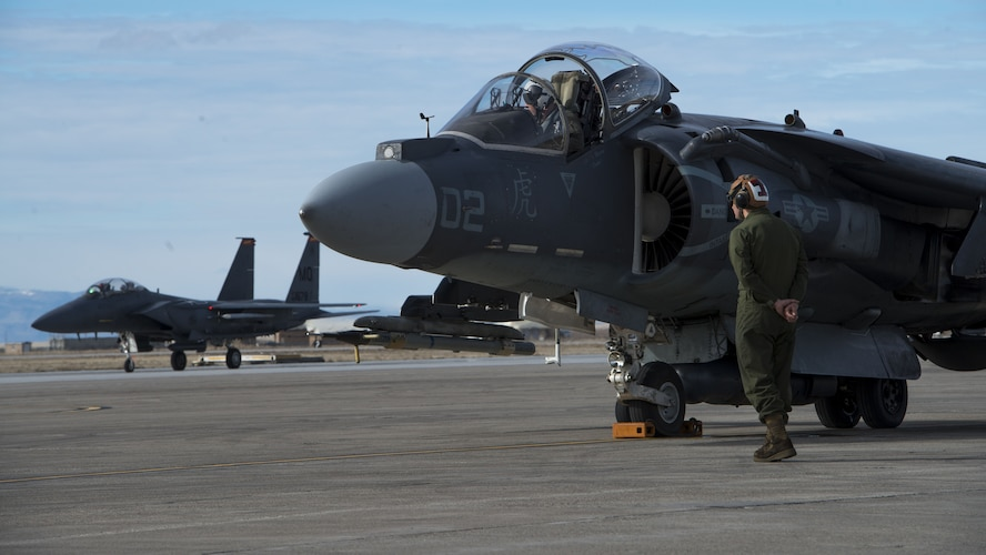 Corporal Tyler Fry, Marine Attack Squadron 542 powerline plane captain, conducts an AV-8B Harrier II pre-flight inspection Jan. 31, 2018, at Mountain Home Air Force Base, Idaho. The Marines worked alongside joint terminal attack controllers, F-15E Strike Eagles and A-10 Thunderbolt IIs to train under cold weather. (U.S. Air Force Photo by Airman 1st Class JaNae Capuno)