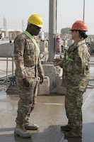 Sgt. Maj. Andre Lawhorn, 35th Infantry Division chemical, biological, radiological and nuclear sergeant major, takes a moment to talk to 35th Inf. Div. materials handler Staff Sgt. Mary Hunt about wash rack operations at Kuwait Naval Base.