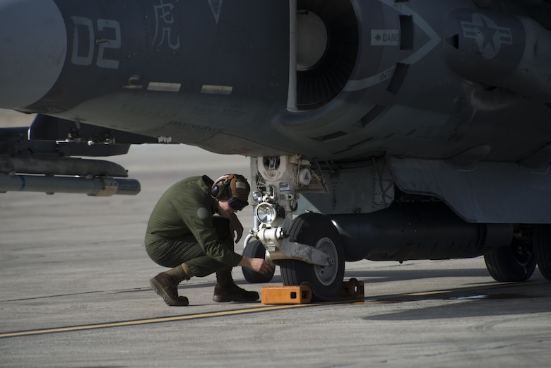Corporal Tyler Fry, Marine Attack Squadron 542 powerline plane captain, inspects the landing gear of an AV-8B Harrier II during a pre-flight inspection Jan. 31, 2018, at Mountain Home Air Force Base, Idaho. The VMA-542 is stationed at Marine Corps Air Station Cherry Point, North Carolina. (U.S. Air Force Photo by Airman 1st Class JaNae Capuno)