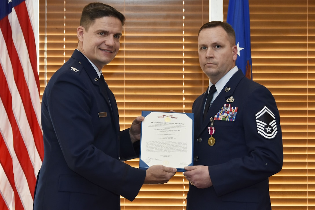 During his retirement ceremony at the Arnold Lakeside Center Jan. 19, Senior Master Sgt. Charles Hoyt, right, receives the Meritorious Service Medal for meritorious service from retired Col. Rodney Todaro. Hoyt retired after serving as the Arnold Air Force Base Senior Enlisted Leader since September 2015. As Senior Enlisted Leader, he advised the commander on training, readiness, effective utilization and development of all Airmen. He ensured that Airmen understood and executed the commander's policies. Additionally, he maintained relationships with local civilian community leaders and provided recommendations to the Complex division chiefs and key staff members on behalf of the enlisted force at Arnold AFB. (U.S. Air Force photo/Rick Goodfriend)