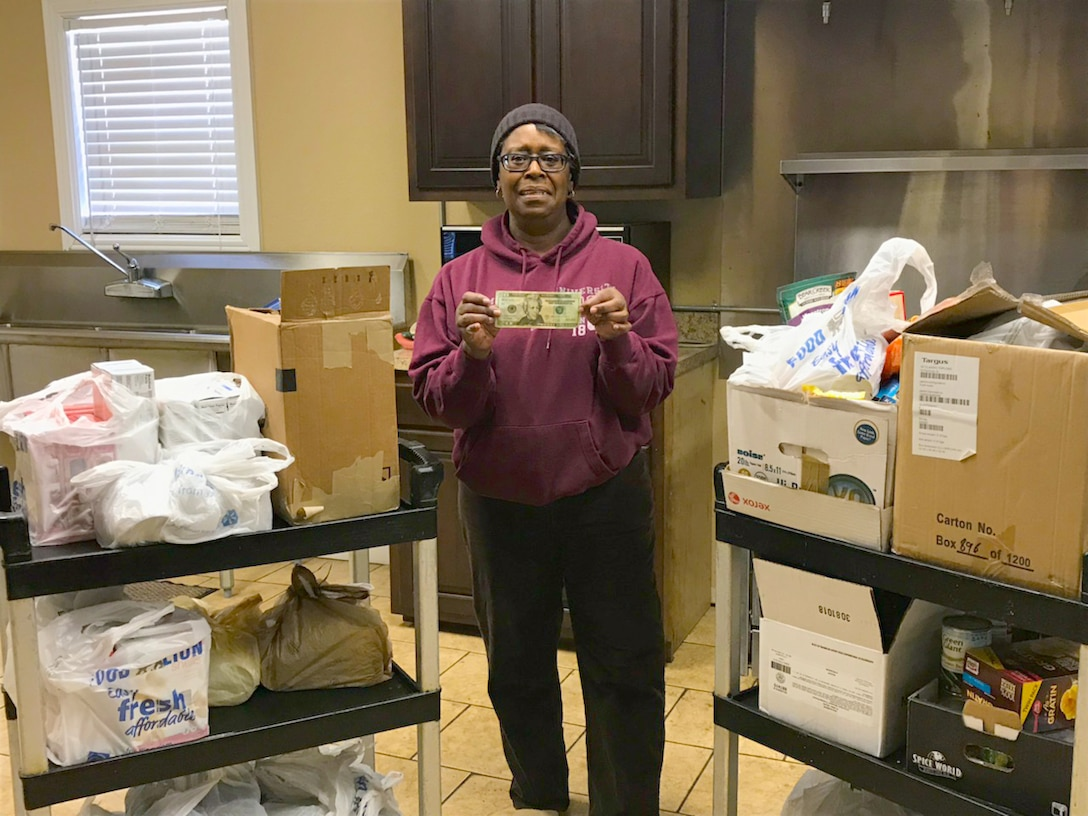 """Jane Chrisman, secretary at the Mt. Zion Baptist Church, Tullahoma, displays food and monetary donations provided by the Arnold Air Force Base African-American Heritage Committee after a recent food drive. The drive was part of a Martin Luther King Jr. Remembrance Walk """"Day of Service"""" event sponsored by the AAHC. More than 200 items were donated to the Mt. Zion Baptist Church Food Locker. (Courtesy photo)"""