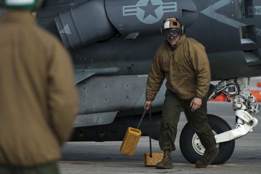 Sgt. Brandon Erway Marine Attack Squadron 542 powerline plane captain, removes the wheel chocks from underneath the AV-8B Harrier II Jan. 31, 2018, at Mountain Home Air Force Base, Idaho. Working in cold weather conditions and side-by-side with the Air Force will help VMA-542 train for its mission. (U.S. Air Force Photo by Airman 1st Class JaNae Capuno)