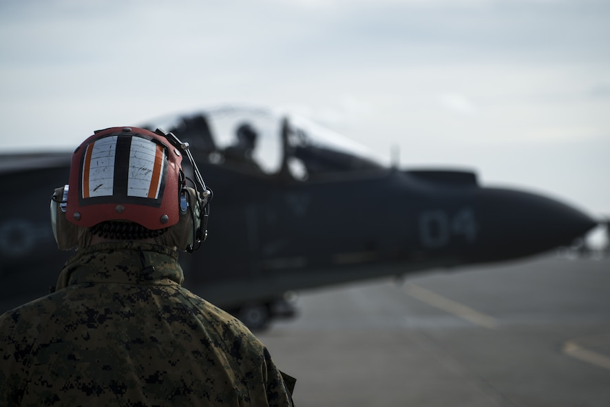 Chief Warrant Officer 2 Alex Harer, Marine Attack Squadron 542 ordinance officer in charge, oversees an AV-8B Harrier II taxing to the runway Jan. 31, 2018, at Mountain Home Air Force Base, Idaho. The Marine Attack Squadron 542 worked alongside joint terminal attack controllers, F-15E Strike Eagles and A-10 Thunderbolt IIs. (U.S. Air Force Photo by Airman 1st Class JaNae Capuno)