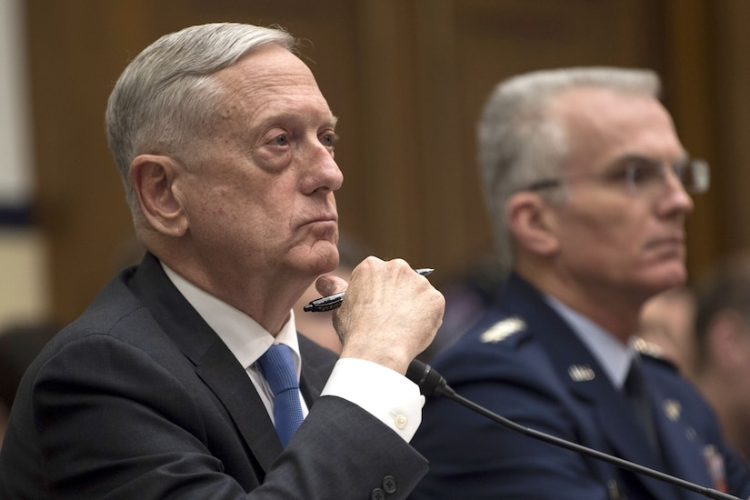 Defense Secretary James N. Mattis and the vice chairman of the Joint Chiefs of Staff sit behind a desk.
