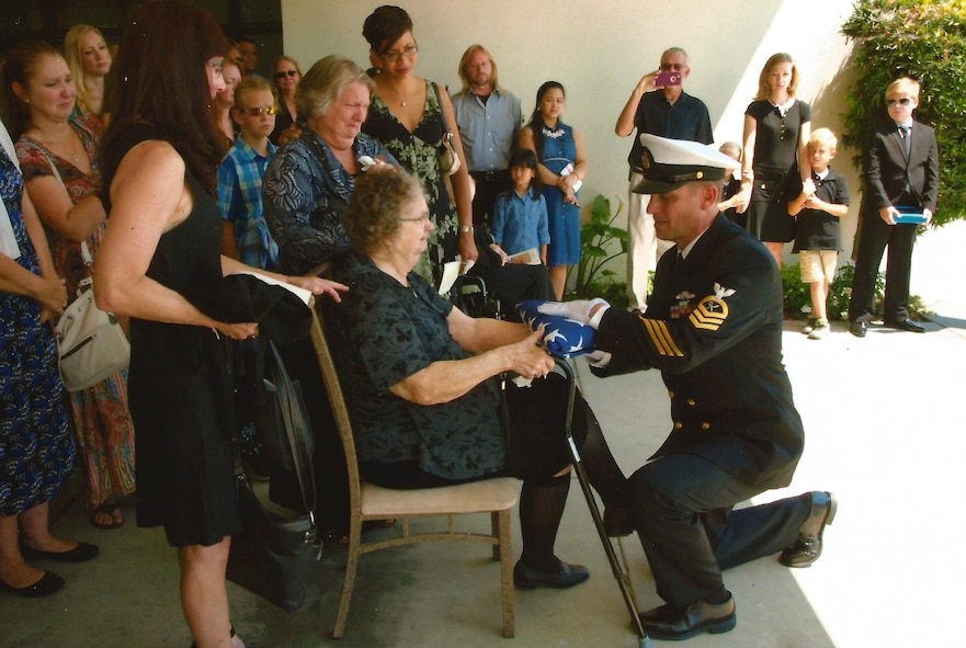 Intelligence Specialist Chief Petty Officer Paul Baumgartner hands a folded flag to his grandmother, Betty Lou Baumgartner, after acting as pallbearer alongside his five brothers at their grandfather Roy's funeral in June, 2017.