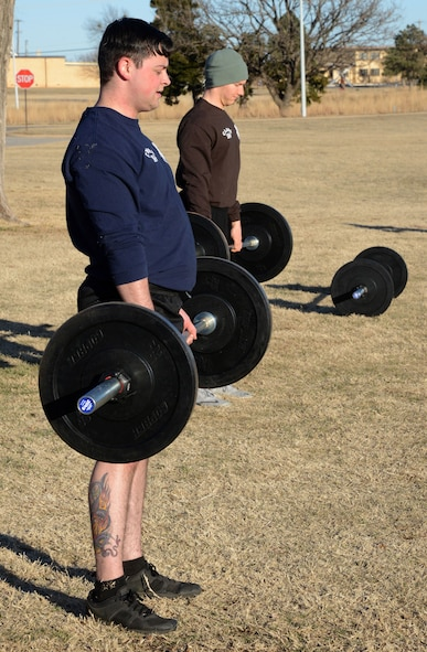 Senior Airman Jourdan Campbell and Staff Sgt. Brandon Gourley perform deadlifts as part of their interval exercises during PT at Airman Leadership School.